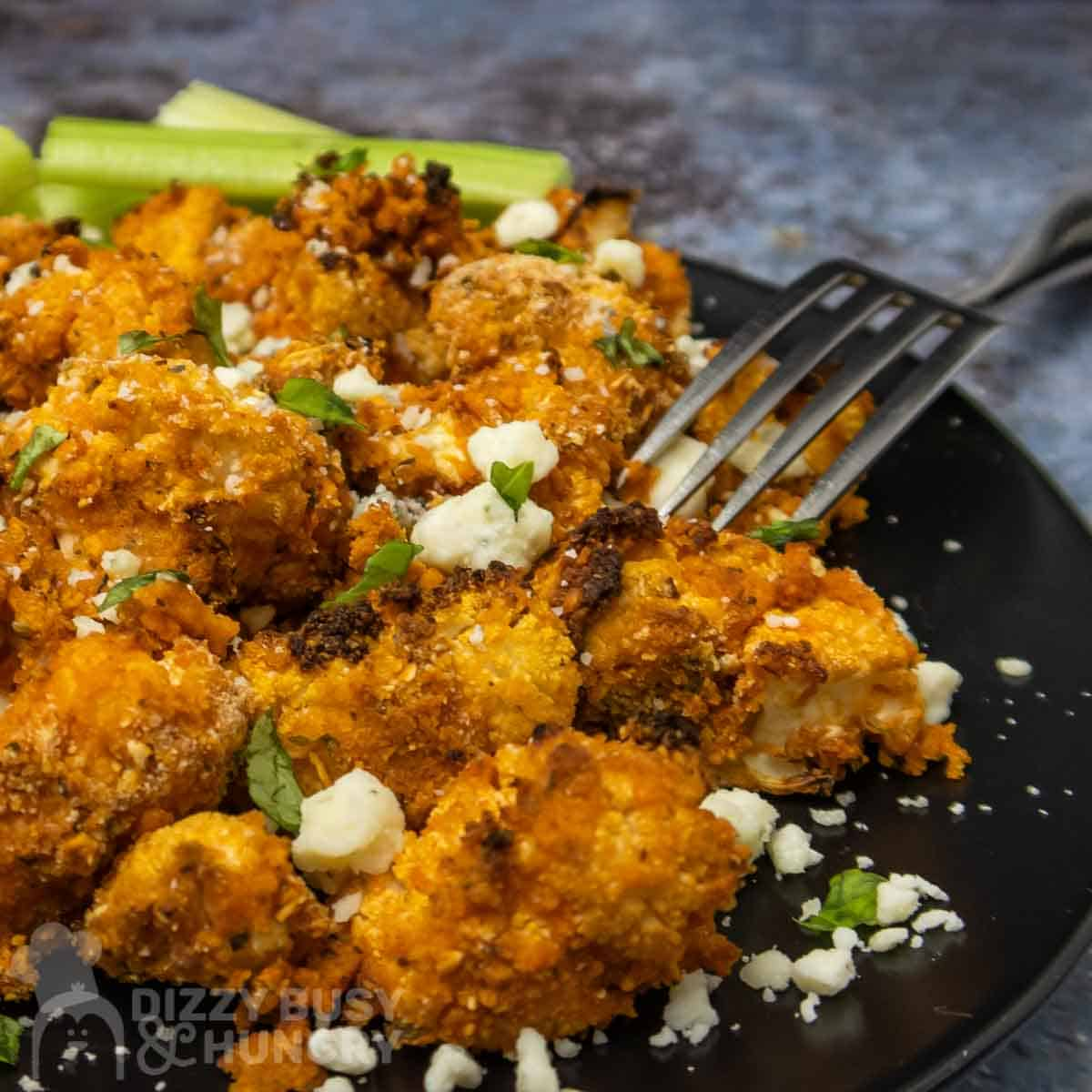 Close up shot of buffalo cauliflower on a black plate sprinkled with cheese crumbles and herbs with a fork and celery on the side.