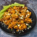Side view of buffalo cauliflower sprinkled with cheese crumbles and herbs with celery on the side.
