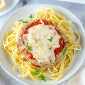Beautifully air fried eggplant parmesan round over a bed of spaghetti topped with chopped parsley.
