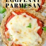 Close up of eggplant parmesan on a white serving dish garnished with chopped parsley.