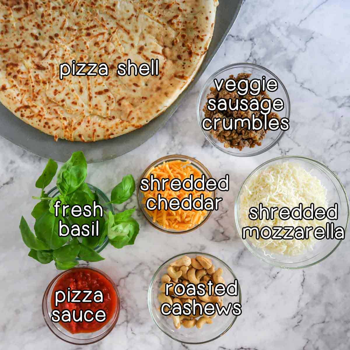 Overhead shot of ingredients- pizza shell, veggie sausage crumbles, fresh basil, shredded cheddar, shredded mozzarella, pizza sauce, and roasted cashews.