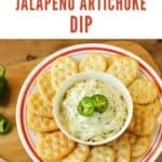 Overhead shot of jalapeno artichoke dip in a white bowl garnished with jalapeno slices with a ring of crackers on a white and red plate.