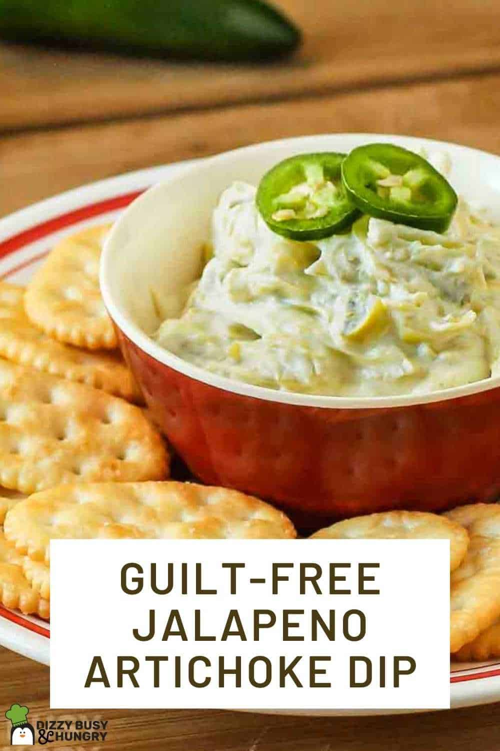 Side view of jalapeno artichoke dip in a red bowl surrounded by a ring of crackers on a red and white plate.