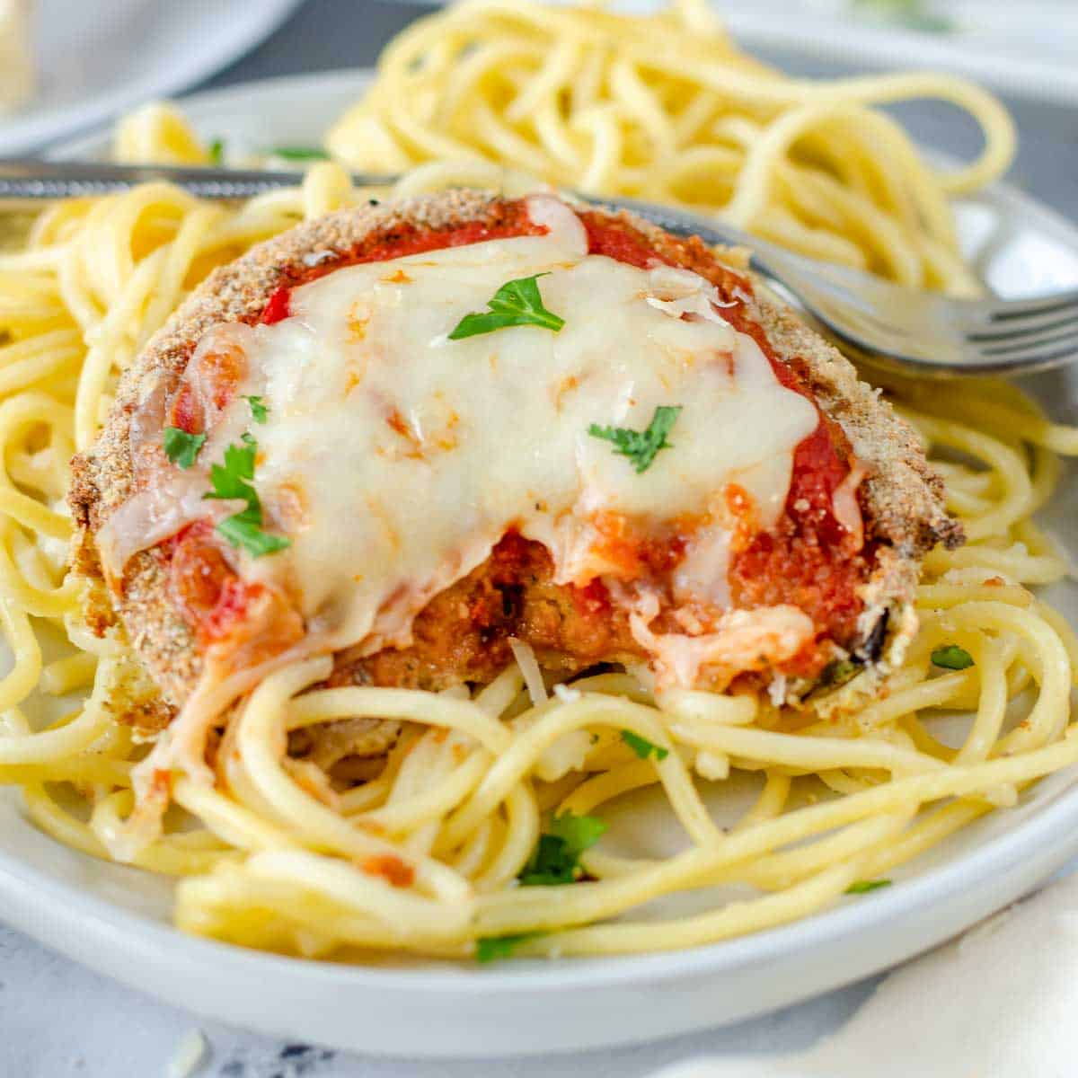 Front view of this easy eggplant parm recipes with a piece cut out to view the yummy inside of the air fried eggplant.