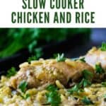 Side view of slow cooker chicken and rice sprinkled with herbs on a black plate.