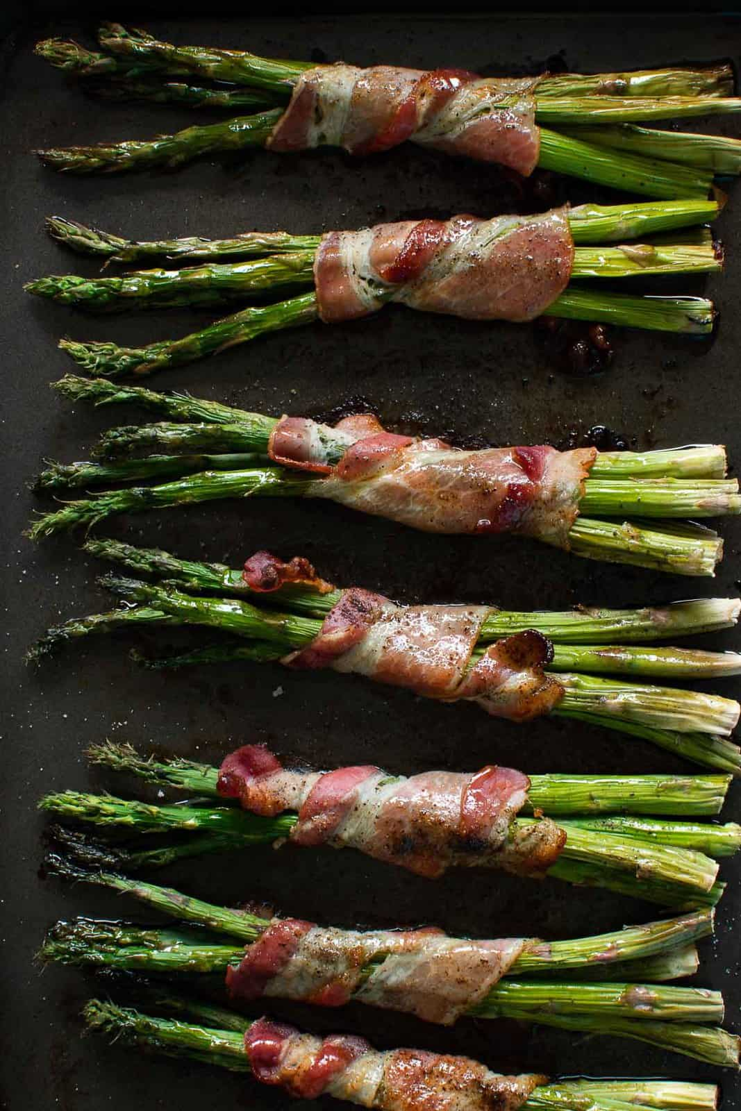 Oven baked bacon wrapped asparagus on a baking sheet.
