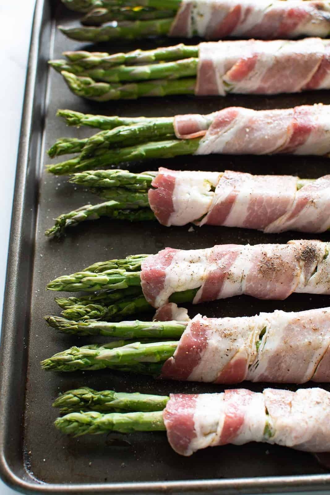 Uncooked asparagus wrapped in raw bacon on a baking sheet.