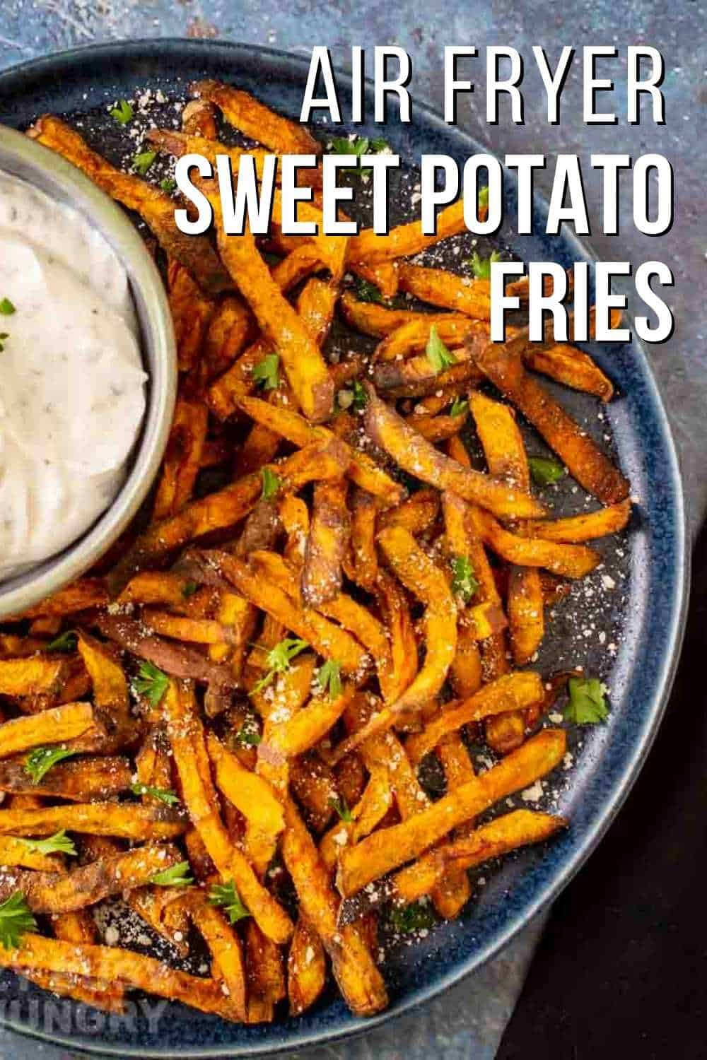 Overhead view of cooked sweet potato fries on a blue plate garnished with crumbled blue cheese and parsley.
