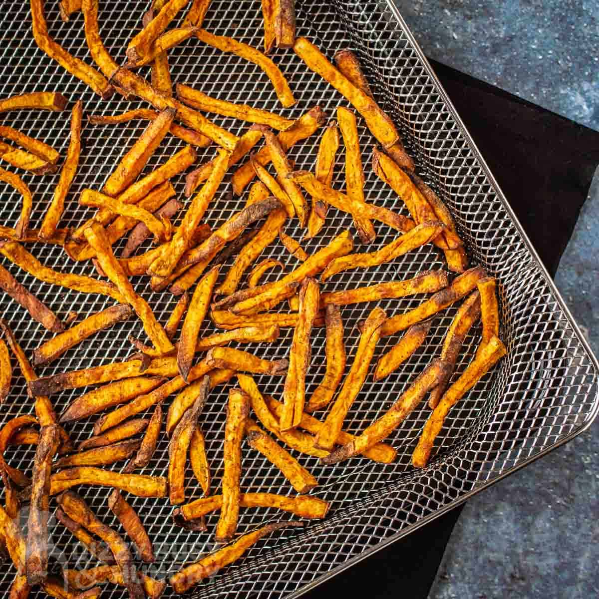 Top down view of air fried sweet potatoes in the air fryer basket sitting on top of a black napkin on a blue speckled surface.