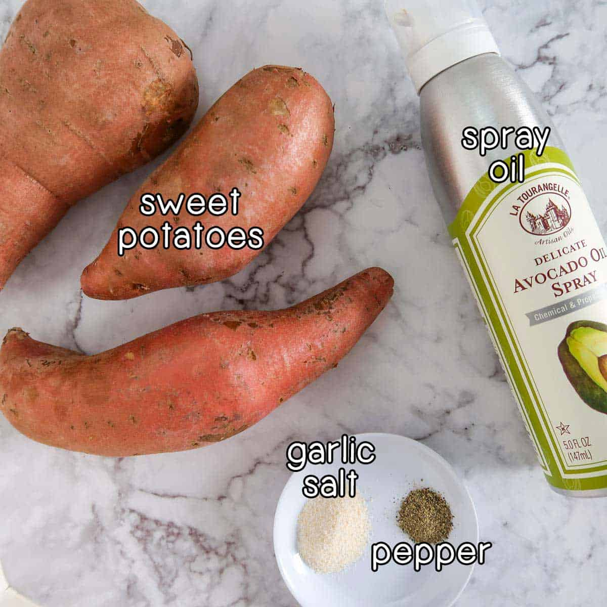 Overhead view of ingredients on a white marble surface, including sweet potatoes, spray oil, garlic salt, and pepper.