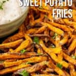 Close up of air fryer sweet potato fries on a blue plate with chopped parsley and crumbled blue cheese garnish.