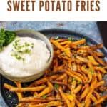 Crispy sweet potato fries on a plate with a side of chipotle mayo dip garnished with chopped parsley.