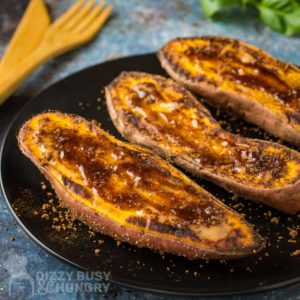 Side view of sweet potatoes topped with a brown sugar mixture that has melted on top of the potato.