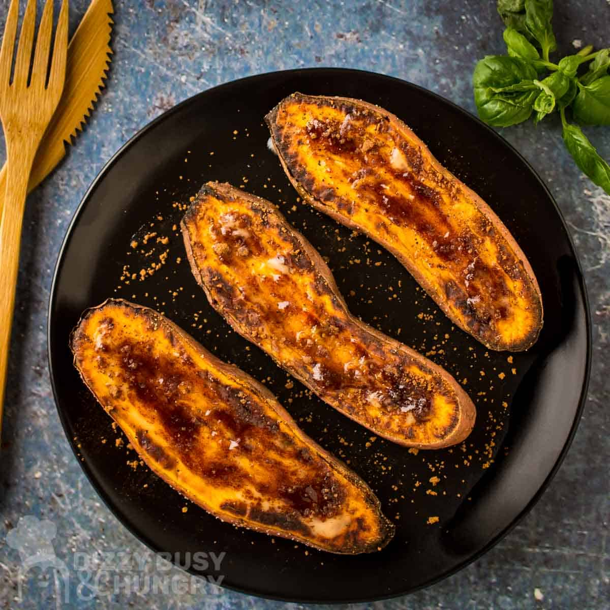 Overhead view of 3 sweet potato halves on a black plate topped with butter and a brown sugar cinnamon mixture.