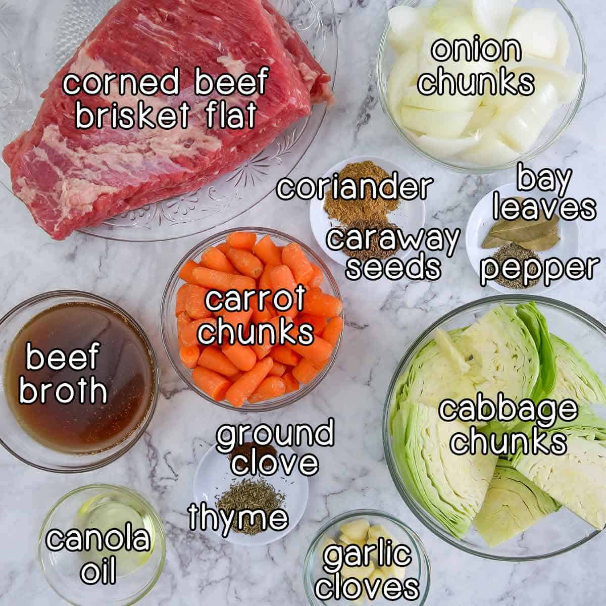 Overhead shot of ingredients- corned beef brisket flat, onion chunks, beef broth, carrot chunks, cabbage chunks, garlic cloves, canola oil, coriander, caraway seeds, bay leaves, pepper, ground clove, and thyme.