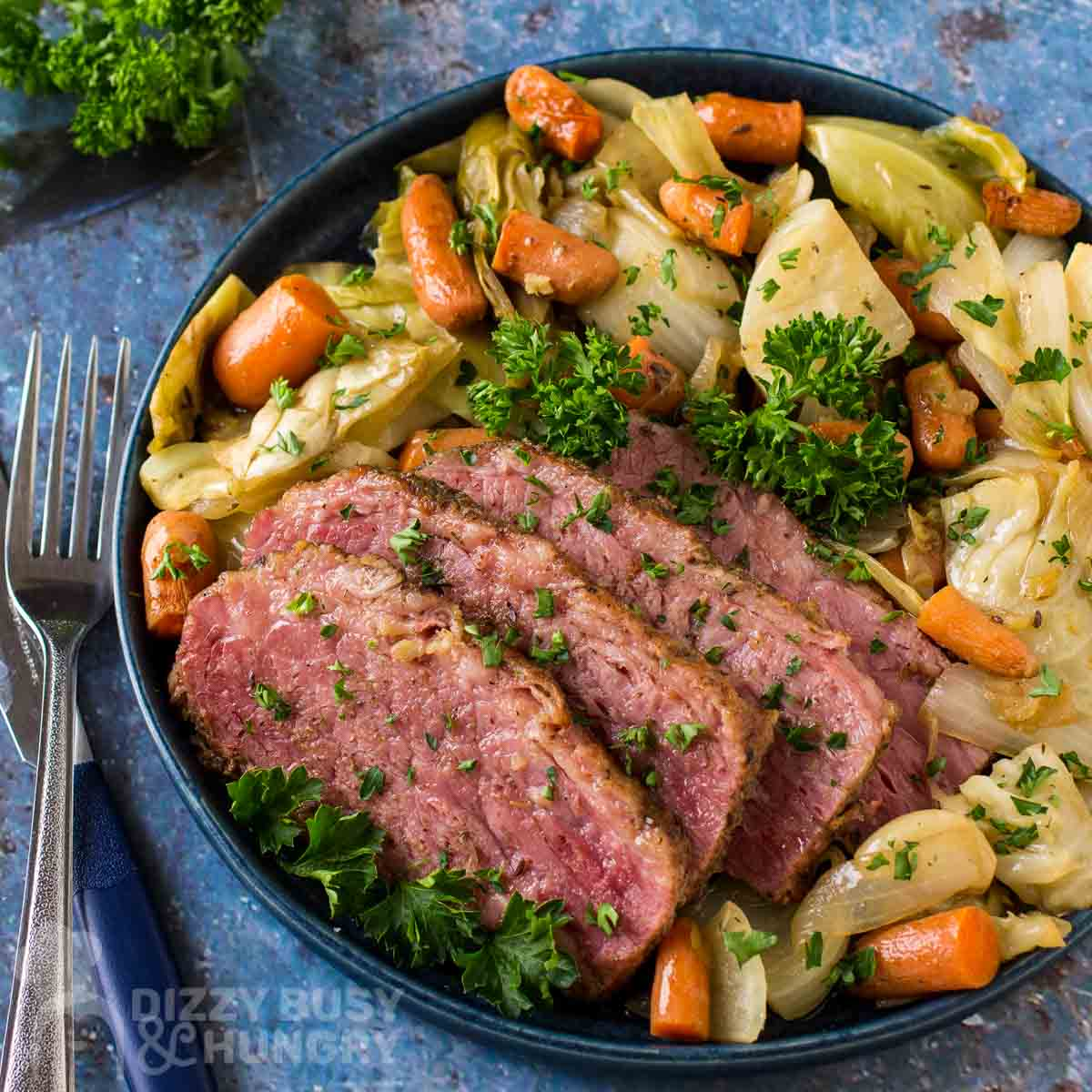 Overhead shot of braised corned beef with vegetables garnished with herbs on a black plate with forks and herbs on the side on a blue cloth.