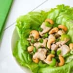 Close up shot of lettuce wrap garnished with cashews and scallions on a white plate with a green cloth on the side.
