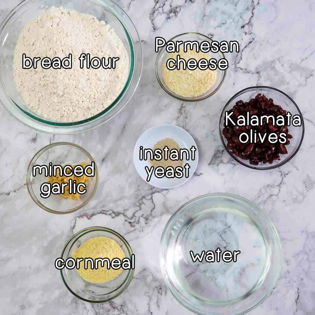 Overhead shot of ingredients- bread flour, parmesan cheese, Kalamata olives, instant yeast, minced garlic, cornmeal, and water.