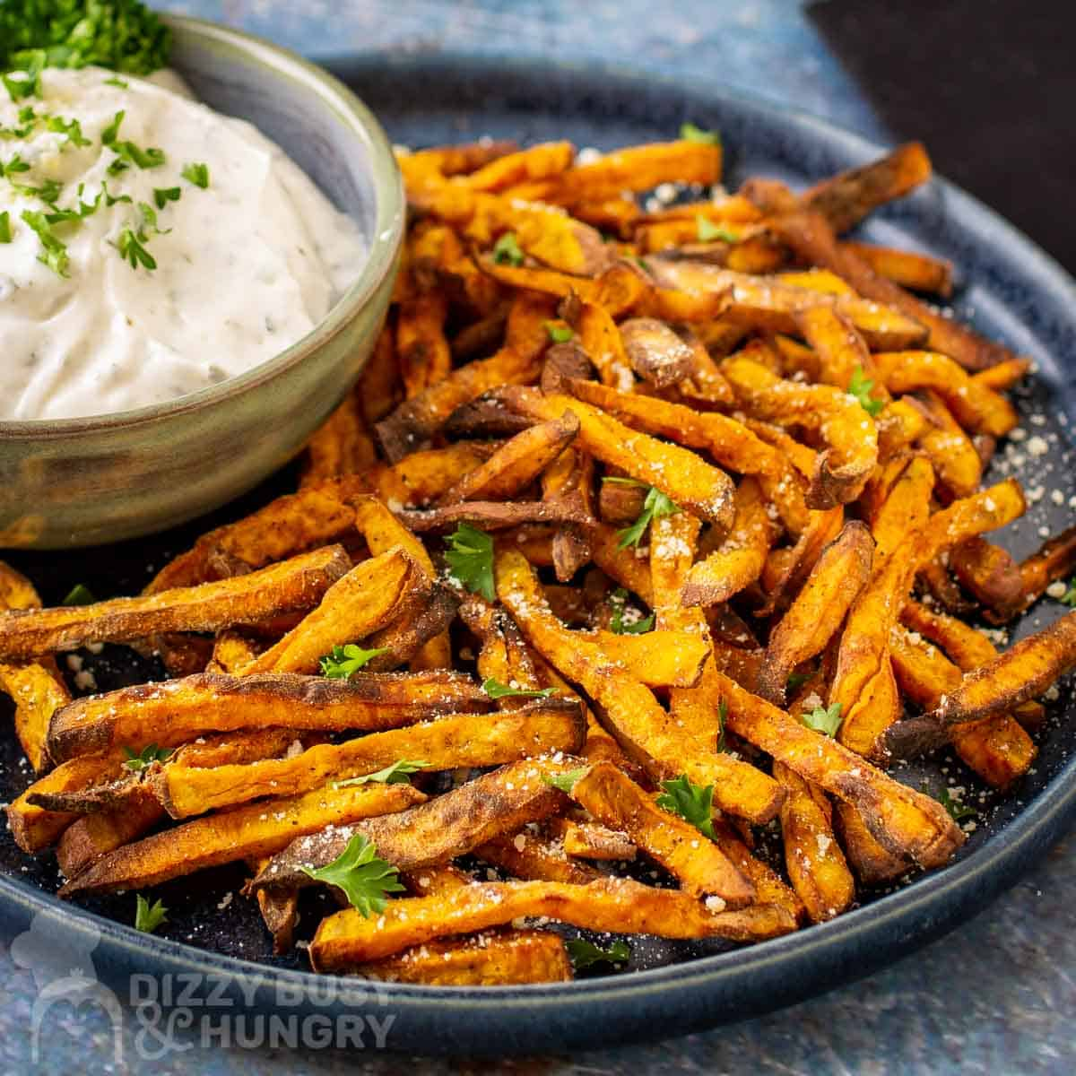 Close up view of the air fried sweet potato fries on a blue ceramic dish on a blue surface with a black napkin in the upper right corner.