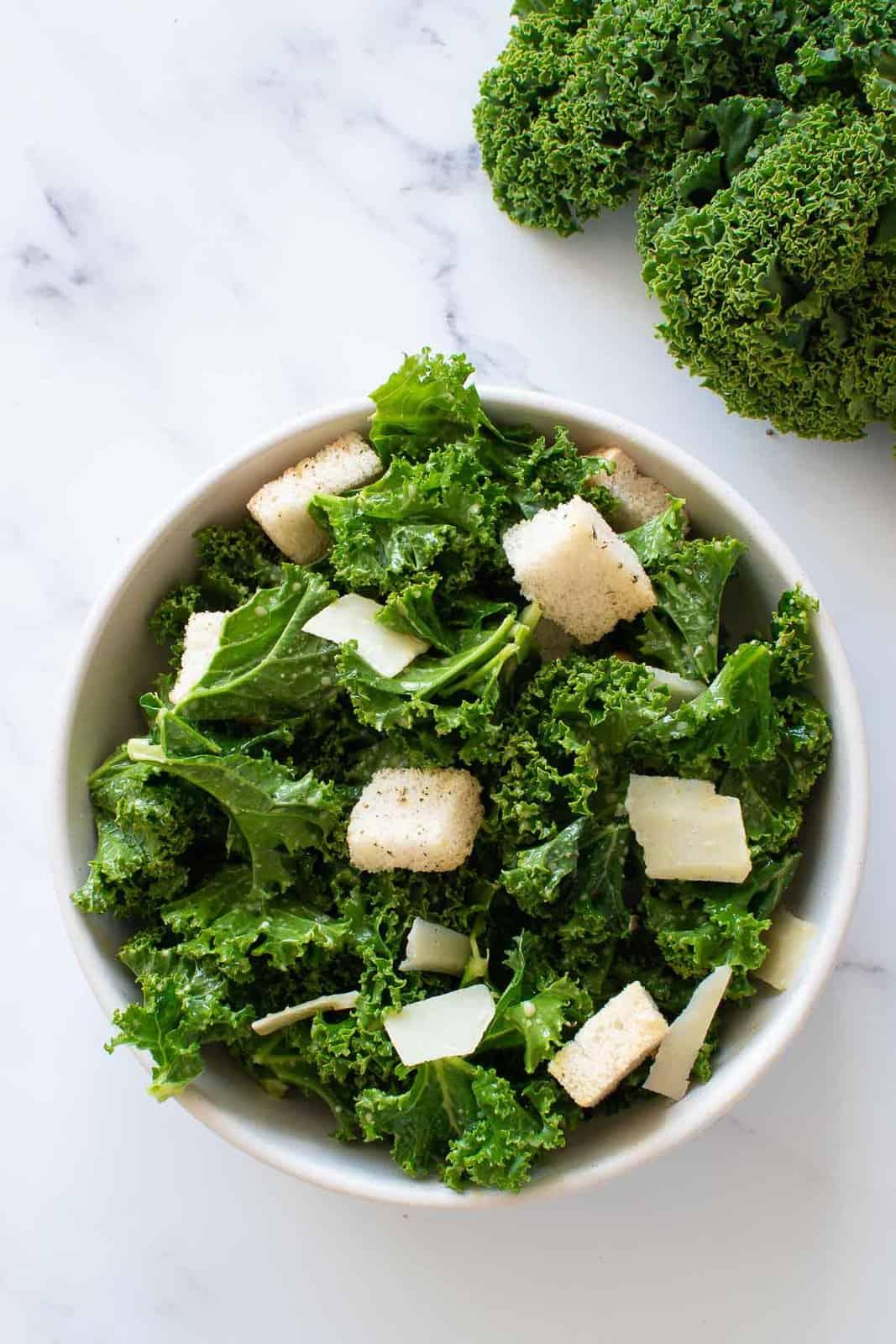 A bowl of kale salad with lemon dressing, croutons and Parmesan.