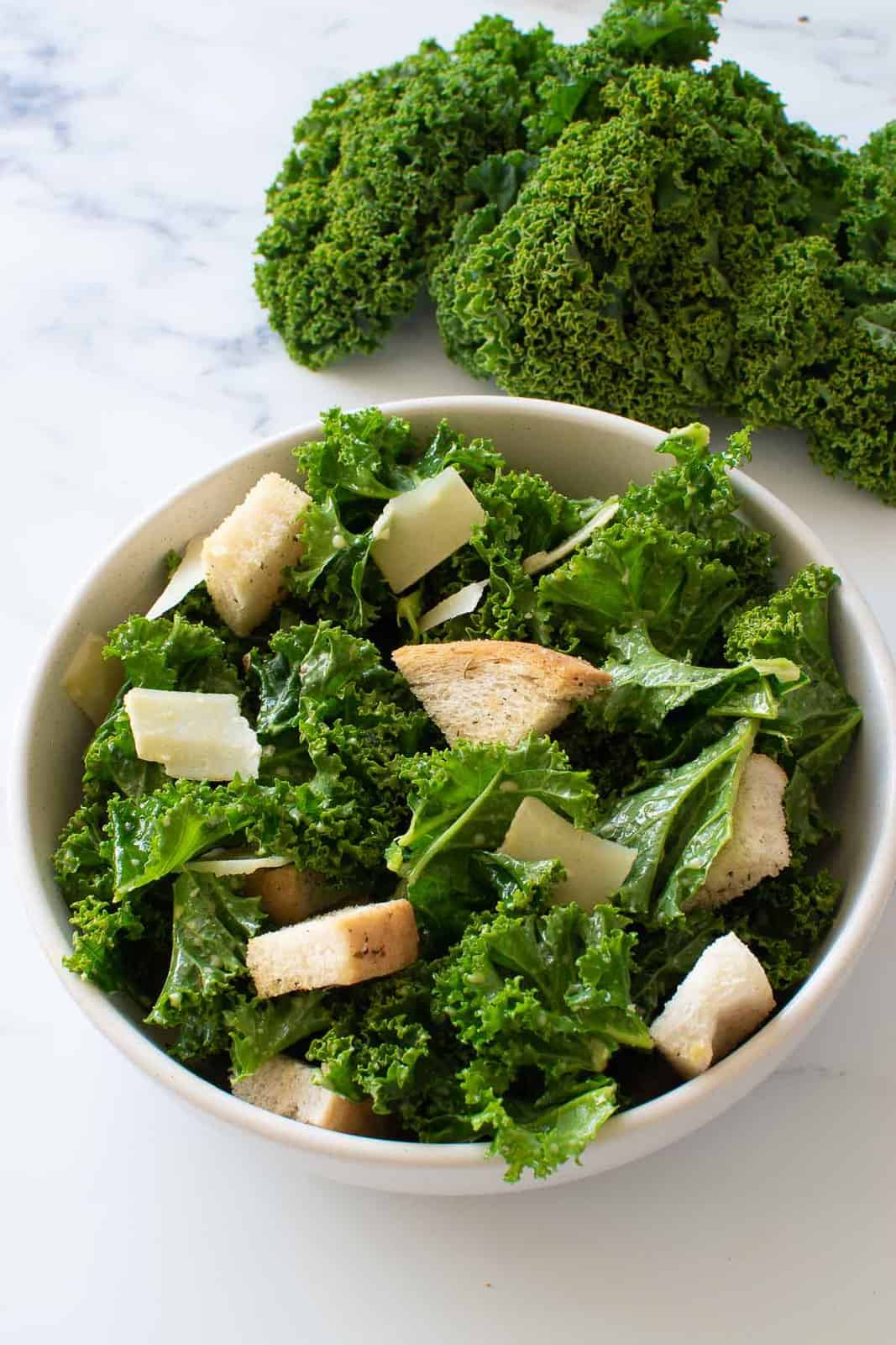 A bowl of kale Caesar salad with Parmesan and croutons.