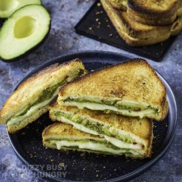 Side shot of multiple triangle halves of avocado grilled cheese on a black plate with more on a black plate and an avocado in the background.
