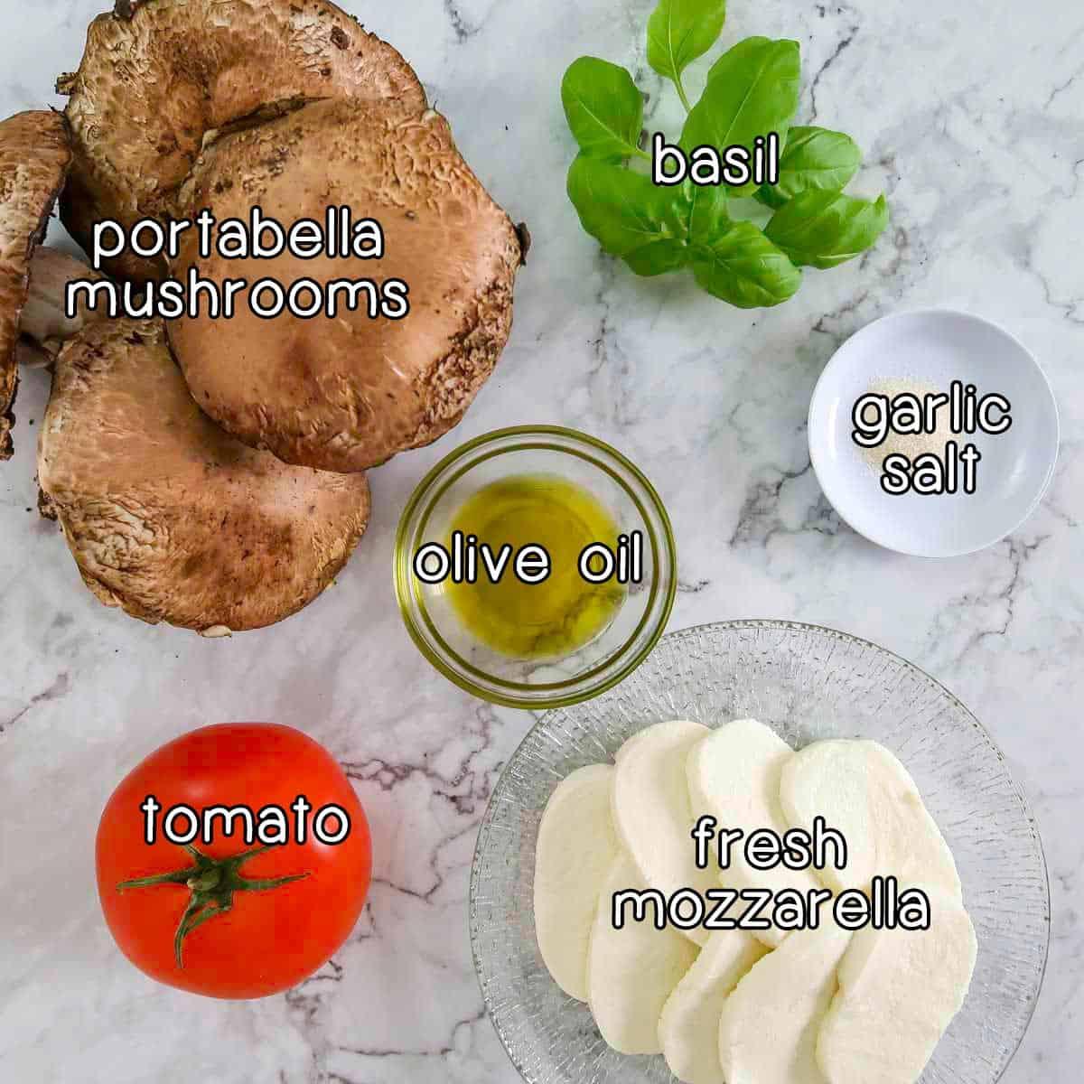 Overhead shot of ingredients- portabella mushrooms, basil, olive oil, garlic salt, tomato, and fresh mozzarella.