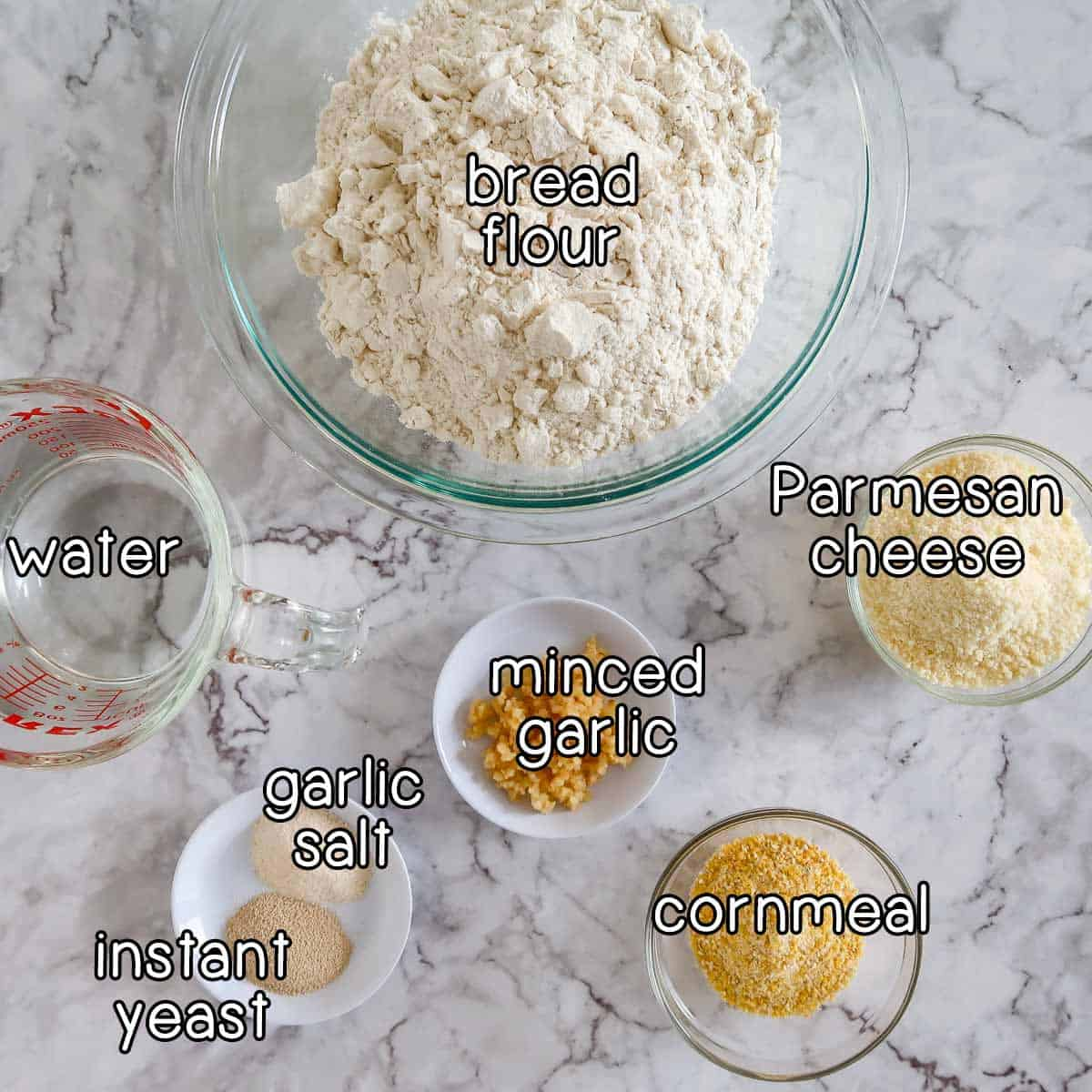 Overhead shot of ingredients- bread flour, parmesan cheese, water, minced garlic, garlic salt, instant yeast, and cornmeal.