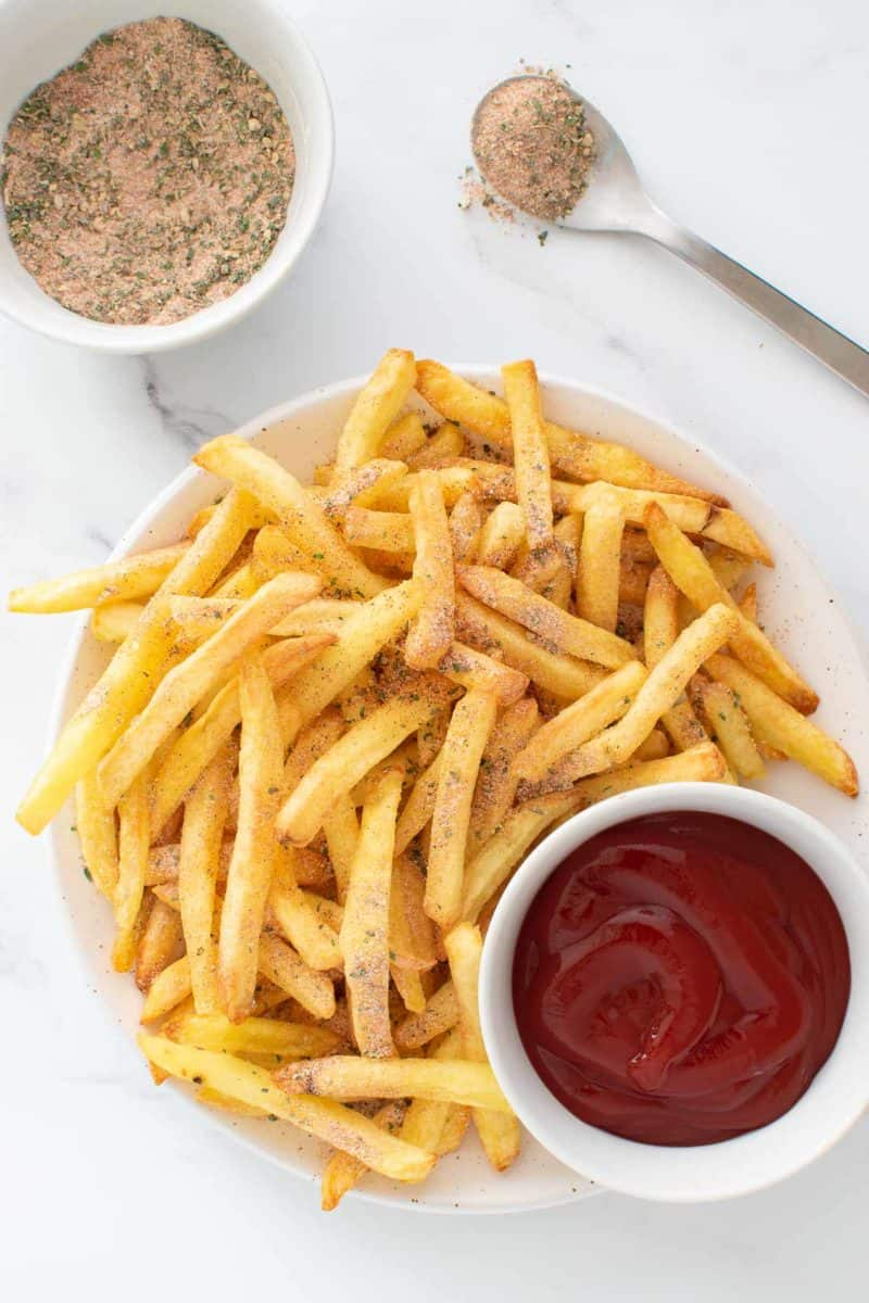 French fries with seasoning, and a bowl of ketchup on the side.