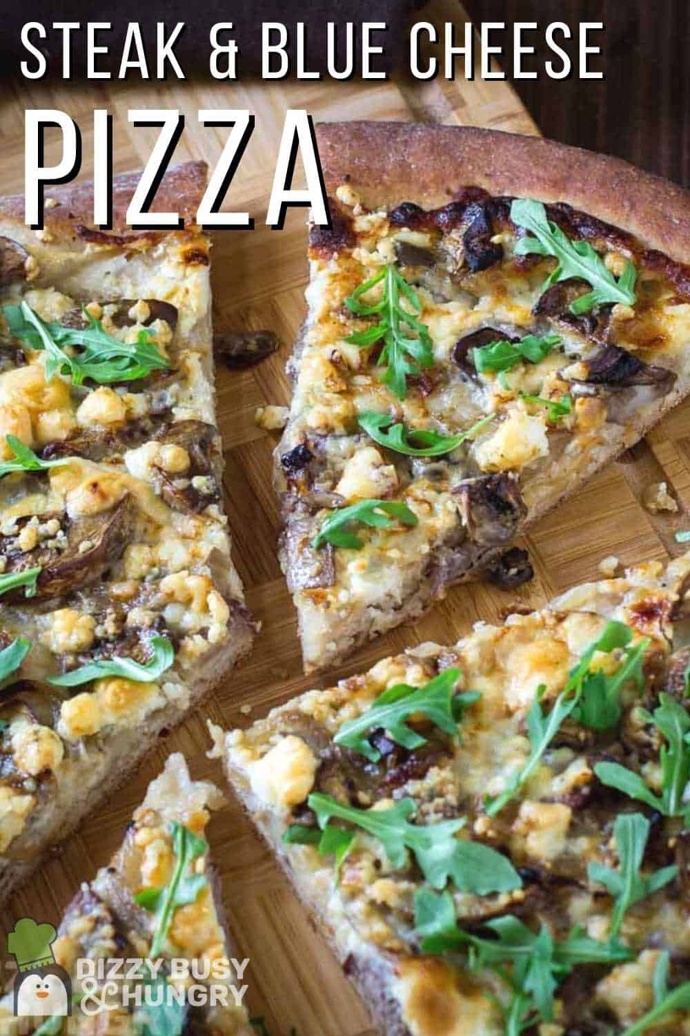 Side angled shot of multiple slices of steak pizza garnished with arugula on a wooden cutting board.