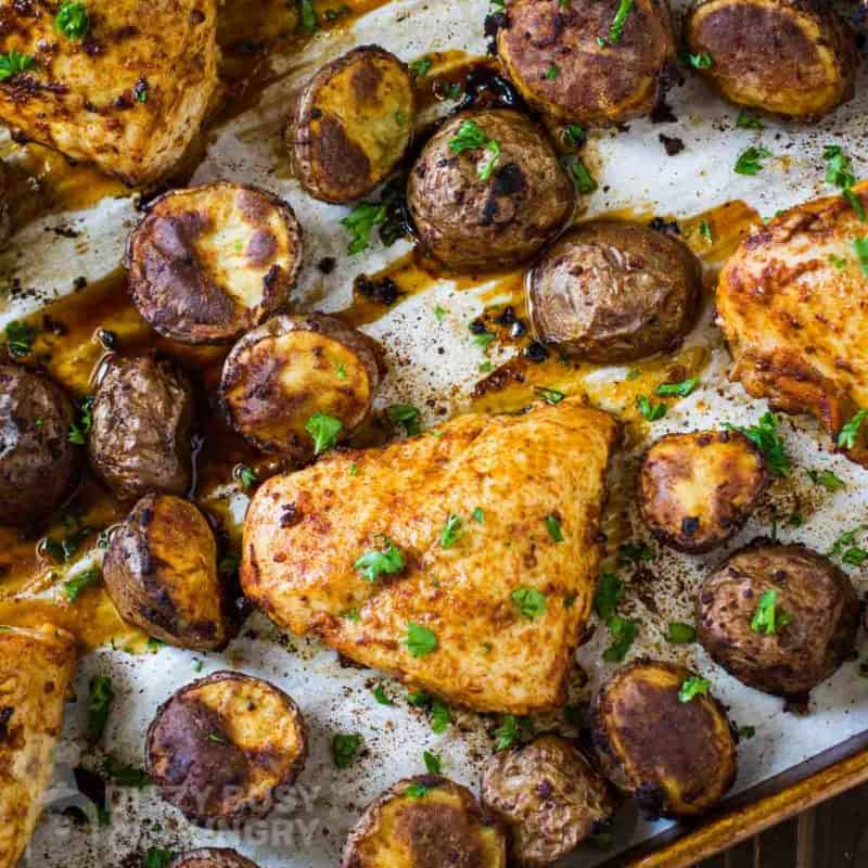 Overhead shot of chicken tray bake on a baking sheet lined with parchment paper garnished with herbs.