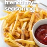 French fries and a small bowl of ketchup on a white plate.