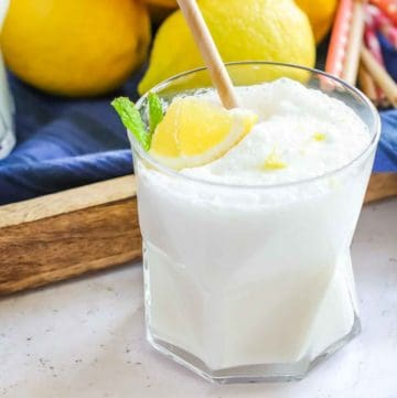 Side shot of frosted lemonade in a clear glass with two straws and a lemon and mint as a garnish with a blue cloth and lemons in the background.