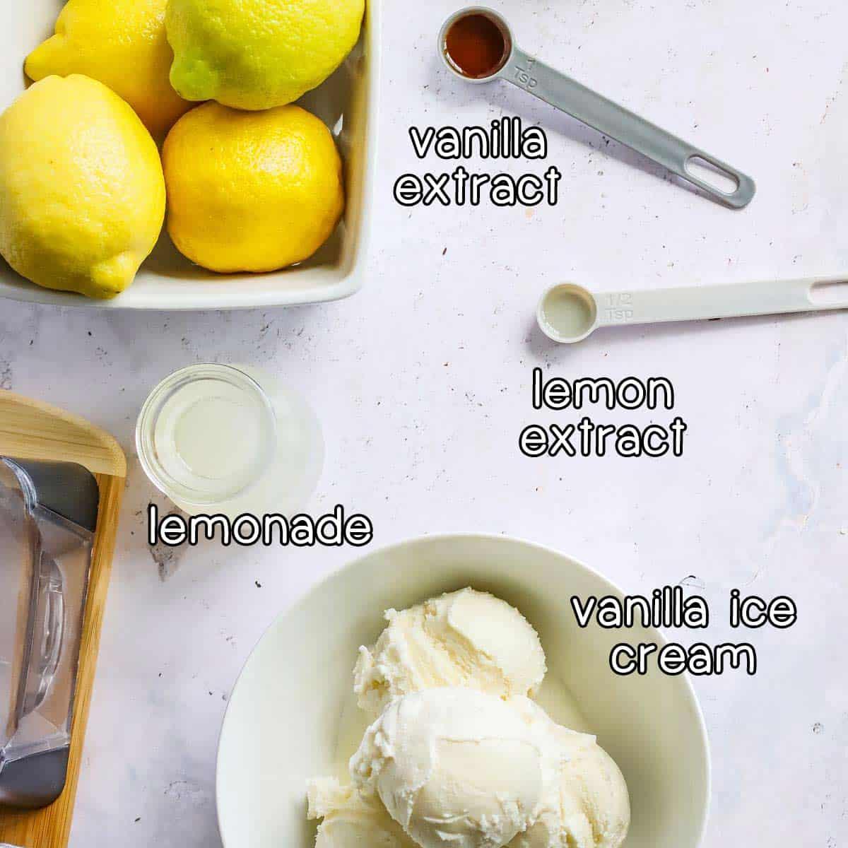 Overhead shot of frosted lemonade ingredients- vanilla extract, lemon extract, lemonade, and vanilla ice cream.