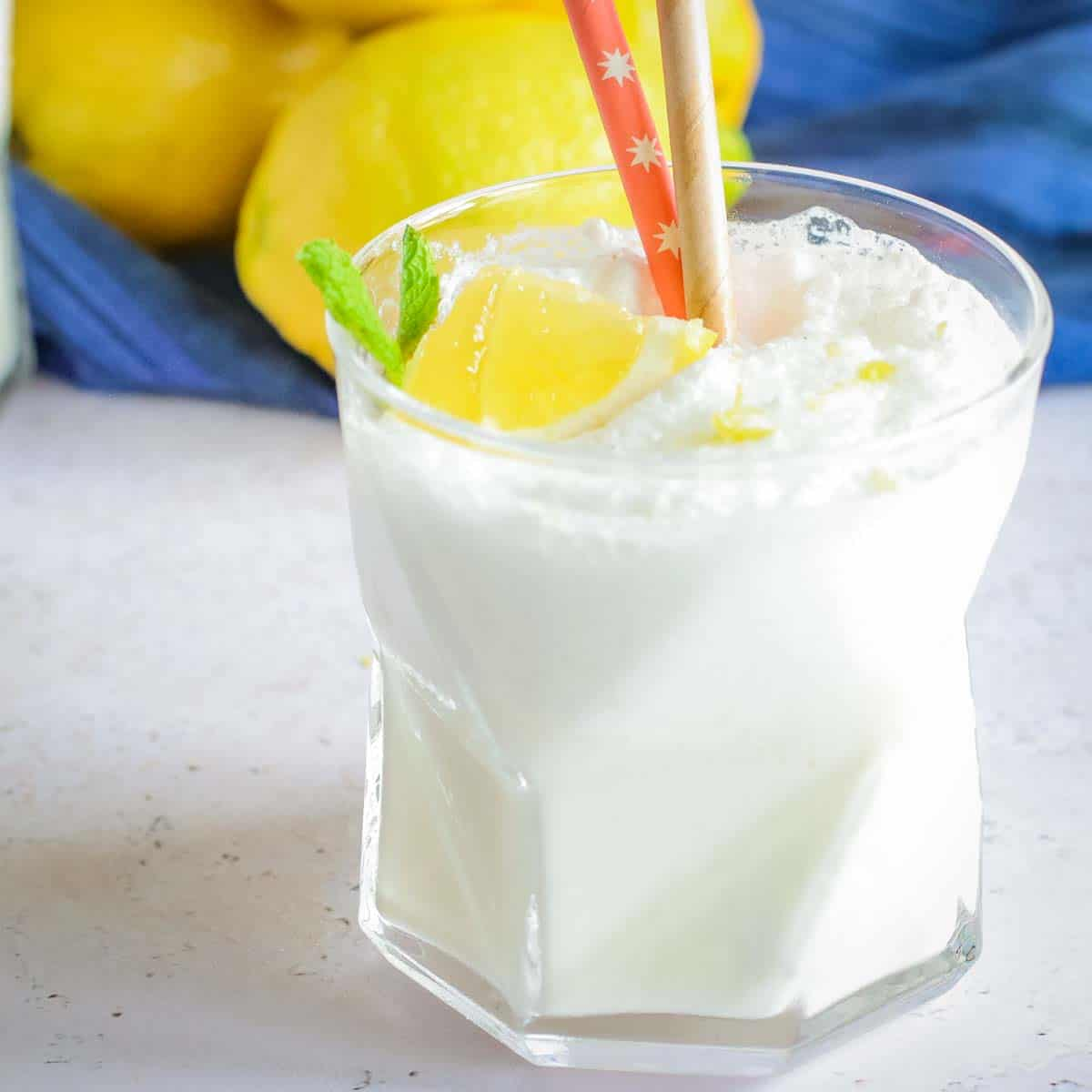 Close up side shot of a chick fil a frozen lemonade in a clear glass with two straws and a lemon and mint as a garnish with a blue cloth and lemons in the background.