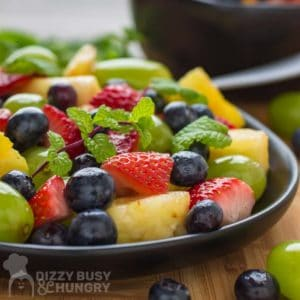 Side shot of berry fruit salad with a mint garnish on a black plate.