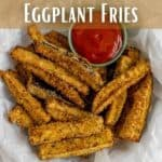 Eggplants fries on a pape towel-covered plate with a small dish of ketchup.