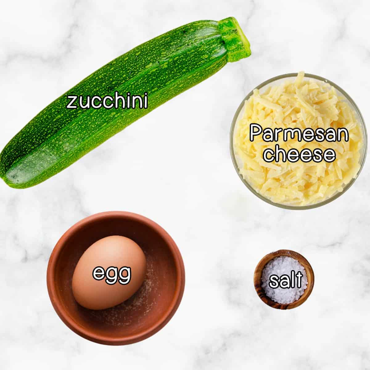 Overhead shot of ingredients- zucchini, parmesan cheese, an egg, and salt.