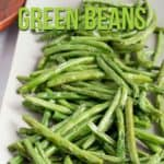 Green beans on a white tray with a wooden spoon.