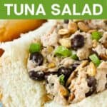 Close up side view of tuna salad sandwich garnished with herbs on a light blue plate.