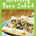 Side shot of tuna salad sandwich garnished with herbs on a light blue plate on a blue plaid cloth.