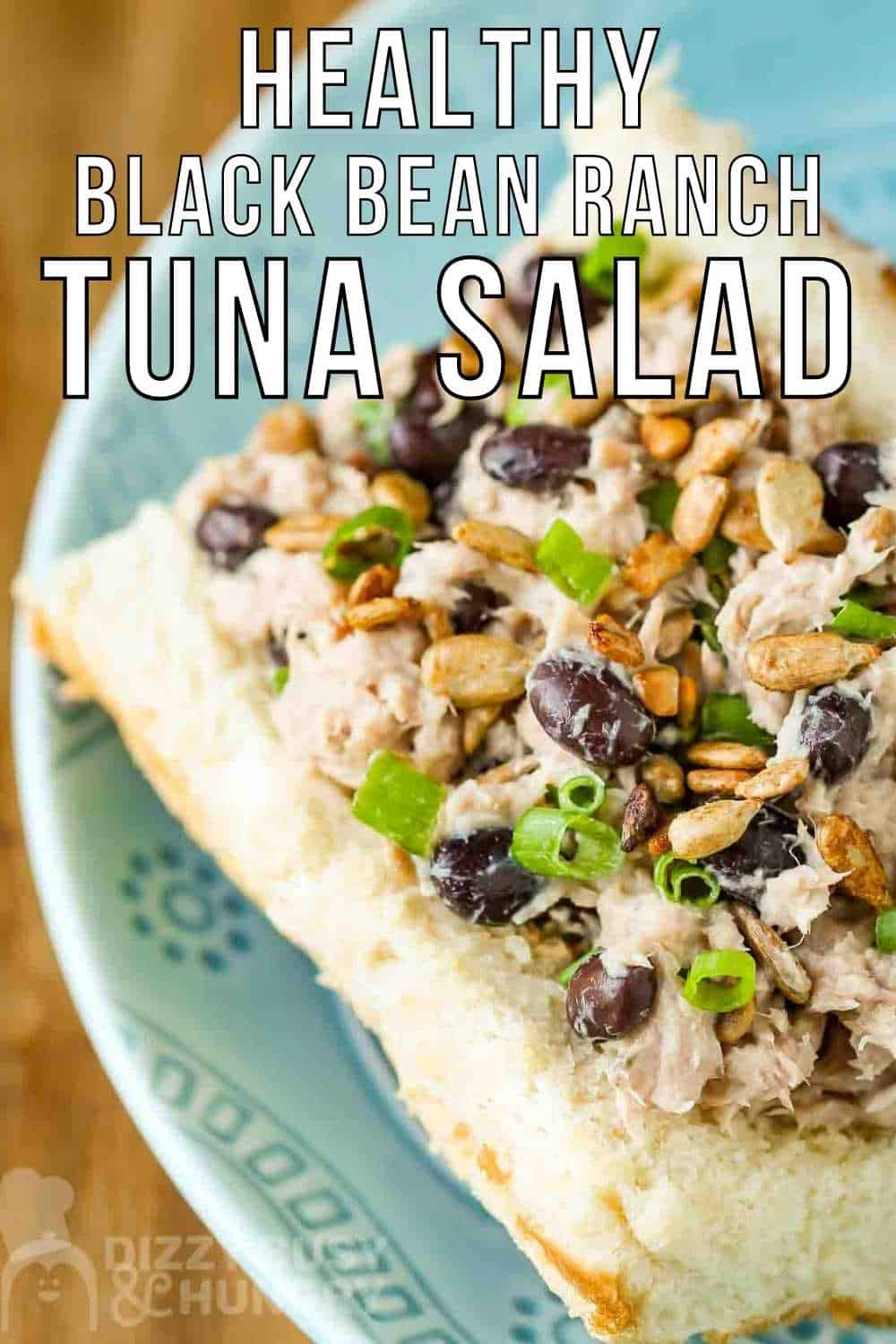 Close up view of tuna salad sandwich garnished with herbs on a light blue plate.