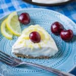 Close up shot of a slice of lemon pie garnished with a whole cherry on a blue plate with a fork, lemon slices, and more cherries on the side.