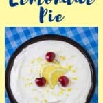 Overhead shot of a whole lemon pie on a black plate garnished with sliced lemons and cherries on a blue picnic cloth.