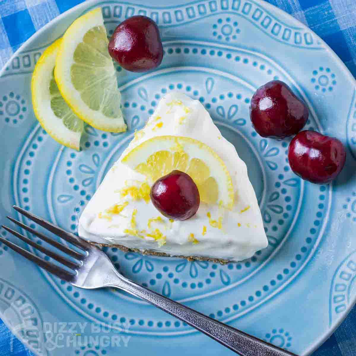 Overhead shot of a slice of lemon pie garnished with a whole cherry on a blue plate with a fork, lemon slices, and more cherries on the side.