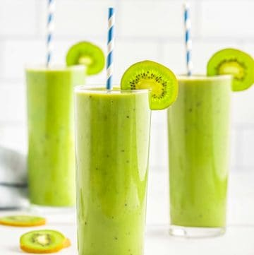 Side shot of kiwi banana match smoothie in a tall clear glass with a slice of kiwi and a straw with more glasses in the background.