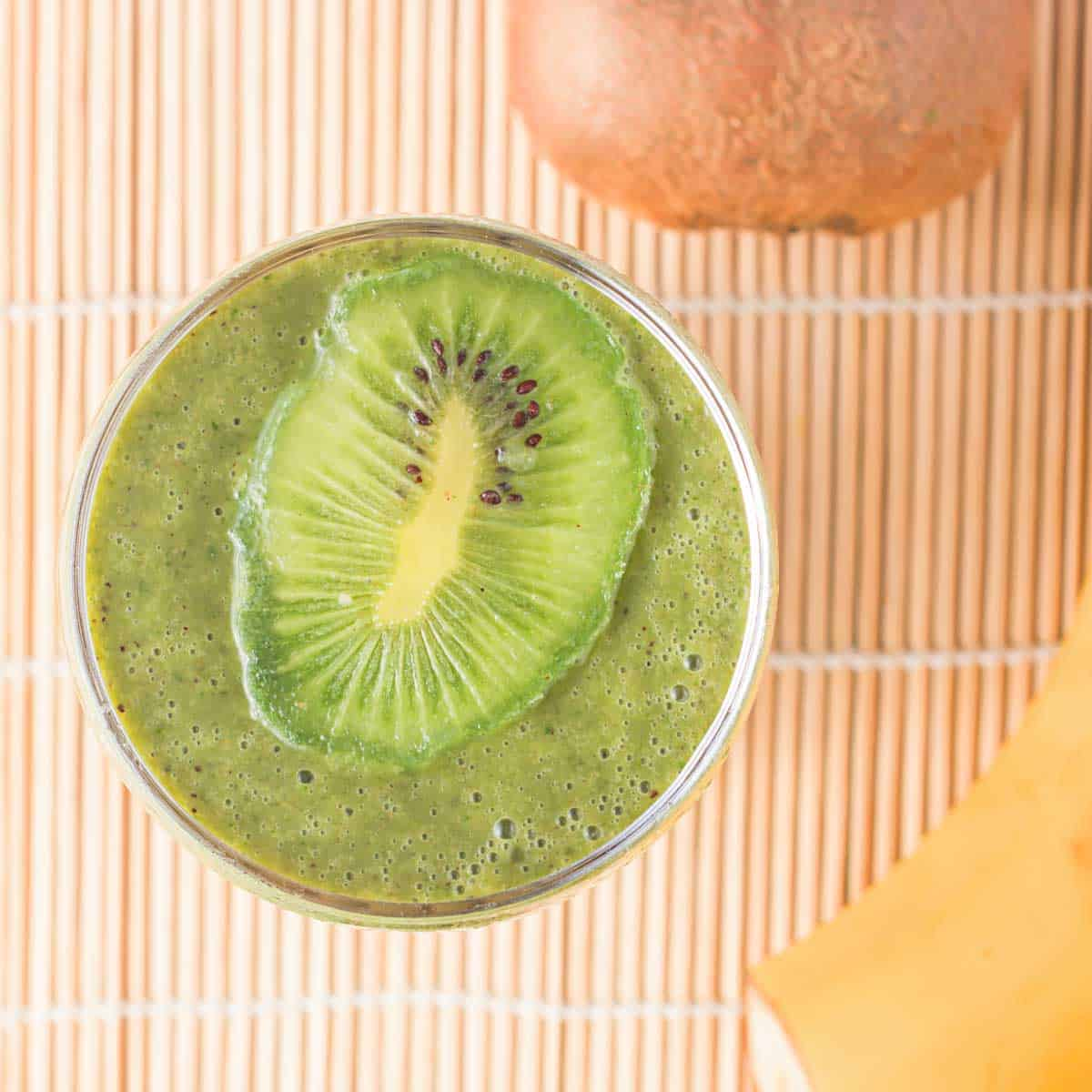 Overhead shot of kiwi smoothie with a sliced kiwi on top in a clear glass on a bamboo mat.
