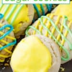 Close up shot of six lemon cookies with blue, yellow, and blue icing on a brown surface.