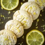 Overhead close up shot of multiple cookies stacked on each other in a diagonal line with lemon shavings and sliced lemons on the side.