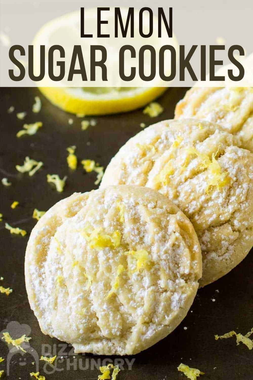 Close up shot of three lemon cookies laying on each other garnished with lemon shavings with a lemon slice in the background.